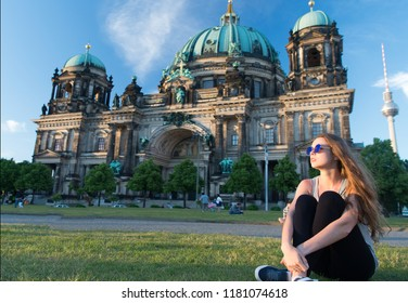 thoughtful girl tourist sitting in germany near berlin cathedral. berlin cathedral view in germany with sitting girl. building tomorrow world today. travel around europe. life is awesome