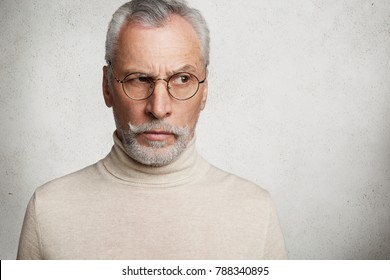 Thoughtful grandfather has grey hair, mustache and beard, dressed casually, looks aside through spectacles, being deep in thoughts, analyzes his actions and different life situations isolated on white