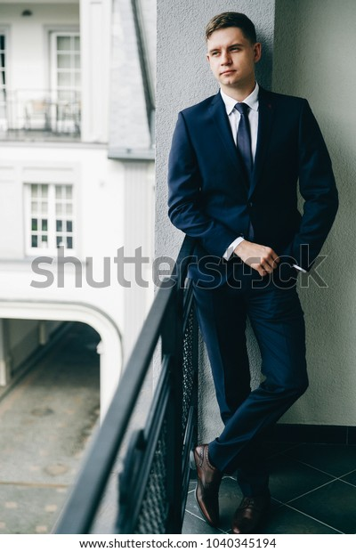 Thoughtful groom in a business suit stands on the balcony