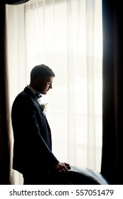 Thoughtful groom holds back of leather chair standing before bright window