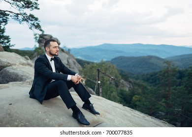 Thoughtful groom sits on the rock