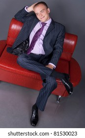 thoughtful guy in a suit sitting on a red couch