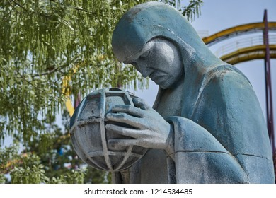 Thoughtful half-body Gotham statue with ball between hands with green tree background and attraction in San Martin de la Vega, Madrid, Spain