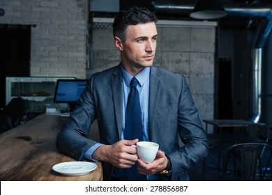 Thoughtful handsome businessman drinking coffee in cafe and looking away