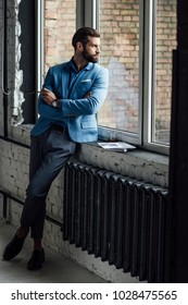 thoughtful handsome man in blue trendy suit looking at window