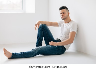 Thoughtful handsome man portrait sitting on floor. Male beauty concept