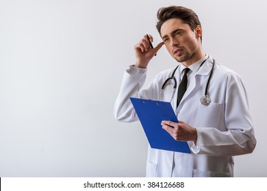 Thoughtful handsome young doctor in white gown and with stethoscope holding a folder and scratching head, on white background