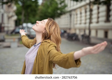 Thoughtful Happy Blond Teen Girl Standing at the Street, Facing Up with Eyes Closed and Wide Open Arms