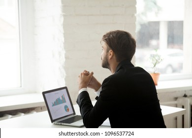 Thoughtful happy businessman distracted from work thinking about new opportunity, risk and challenges, planning business. Concept of motivation, leadership, dreams of future project success. Back view