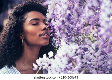 Thoughtful happy young black woman surrounded by flowers
