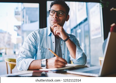 Thoughtful hindu student pondering on creative ideas for writing essay during exam preparation at modern netbook with wireless 4G internet.Contemplative hipster guy in denim jacket drawing sketch