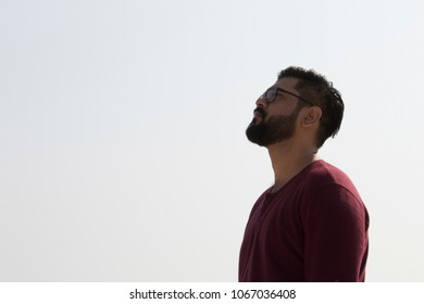 Thoughtful hipster man looking up to the sky