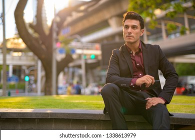Thoughtful Hispanic businessman holding phone and sitting with nature in city