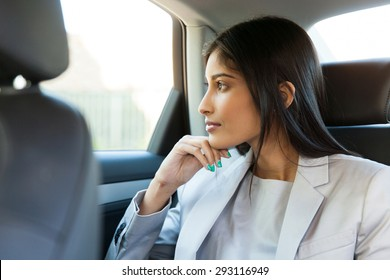 thoughtful indian business woman sitting in car backseat