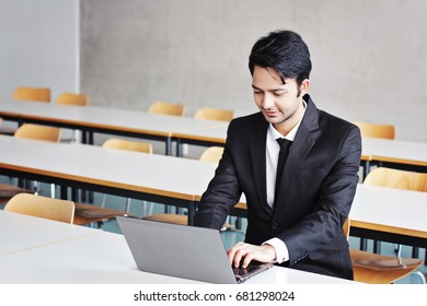 Thoughtful indian businessman working on laptop