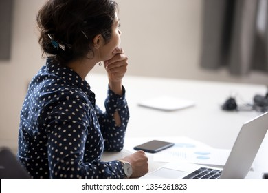 Thoughtful Indian businesswoman looking in distance at workplace, doubting, female employee thinking of difficult question, task, received news, tired office worker have too much work, rear view