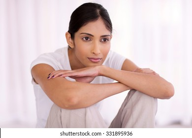 thoughtful indian woman sitting at home