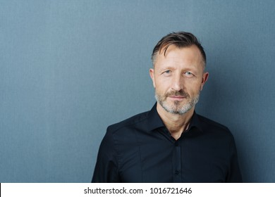 Thoughtful intense middle-aged man standing staring at the camera against a dark grey studio background with copy space