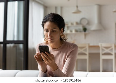 Thoughtful latin woman look at cell screen ponder on web store sales proposition reflect over answer on business offer. Interested young lady mobile phone user sit on sofa download new app for testing