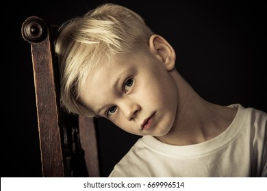 Thoughtful little blond boy sitting on an old wooden kitchen chair tilting his head against the backrest as he stares at the camera