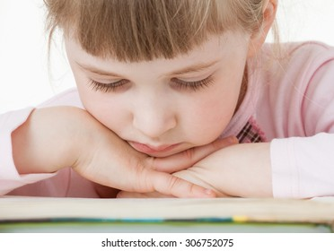 Thoughtful little girl with a books, white background