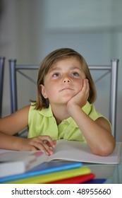 Thoughtful little girl doing homework