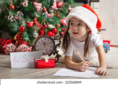 Thoughtful little girl in Santa hat writes letter to Santa Claus near christmas tree