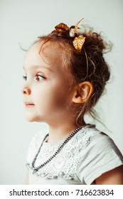 Thoughtful little girl sits before a bright window