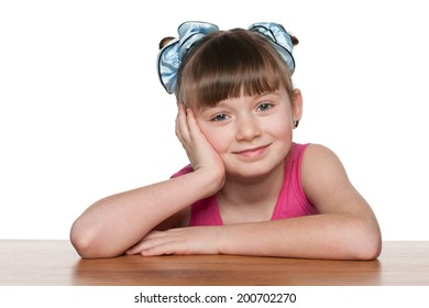 A thoughtful little girl sits at a school desk against the white background