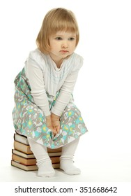 A thoughtful little girl sitting on a stack of books; white background