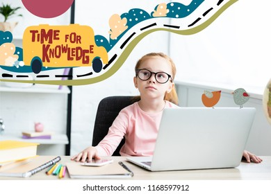 """Thoughtful little schoolchild in eyeglasses looking up while sitting at desk and using laptop with """"time for knowledge"""" lettering"""
