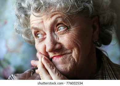 Thoughtful and looking elderly woman face