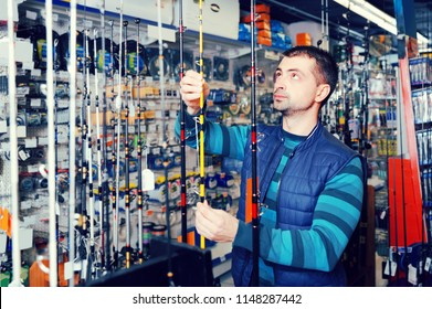 thoughtful male choosing fishing rod for fishing in the sports shop indoors