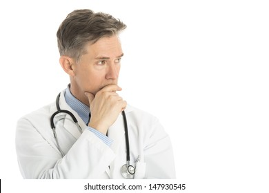 Thoughtful male doctor looking away while standing against white background