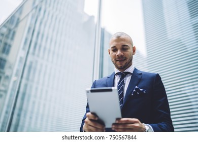 Thoughtful male entrepreneur in formal wear standing on urban settings of big city using touchpad for browsing webpage, prosperous trader checking financial news via portable pc satisfied with income