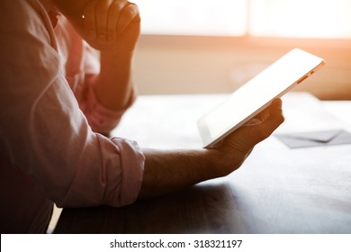 Thoughtful male person looking to the digital tablet screen while sitting in modern loft interior at the table, experienced entrepreneur reading some text or electronic book at the office, filter sun