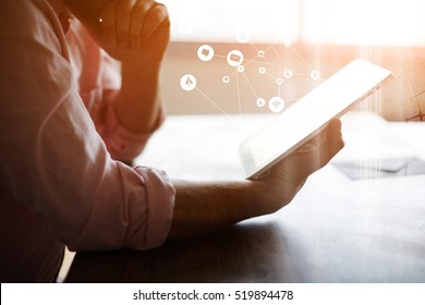 Thoughtful male person looking to digital tablet screen with infographics effects of popular applications and multimedia programs, businessman reading electronic book at  office interior, filter sun