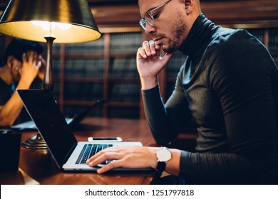 Thoughtful male scientist solving problems with project sitting in public library with new laptop computer, contemplative young professor reading publication online about historian literature