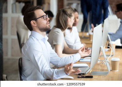 Thoughtful male worker sit in lotus position meditating at workplace, peaceful employee practice yoga in office, controlling emotions and staying calm, businessman clear mind or reach nirvana state