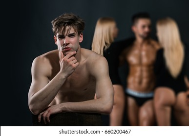 thoughtful man with bare chest near group of people of athletic guy and women in love relations on blurred background, lesbian and gay, betrayal