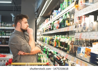 Thoughtful man with a beard looks at bottles with beer in a supermarket. Man wears a shirt, looks at the shelf with bottles of beer and thinks. Buyer buys a beer at a supermarket.