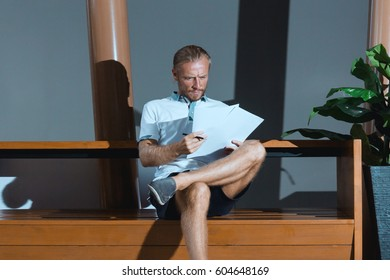 Thoughtful man browsing papers. Serious confident man sitting and browsing papers. Horizontal indoors shot.