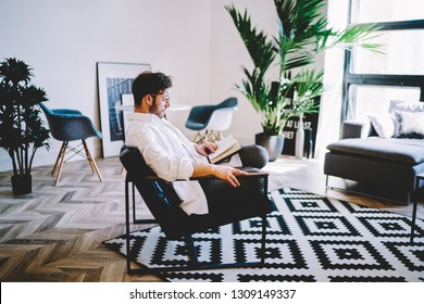 Thoughtful man dressed in casual look resting in comfortable chair and reading interesting bestseller about youth lifestyle, young hipster guy relaxing during literature hobby in home interior