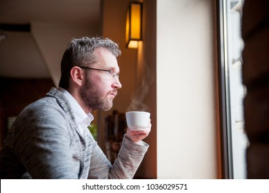 Thoughtful man drinking coffee in the cafe and looking out window