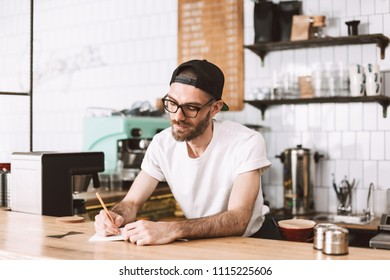 Thoughtful man in eyeglasses and cap standing behind bar counter and writing in notepad while working in cafe