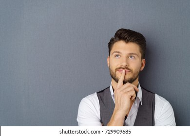 Thoughtful man with his finger to his lips looking up into the air with a pensive expression over a grey studio background with copy space