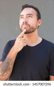 Thoughtful man holding finger on chin and looking up. Bearded young man standing with finger on chin and thinking on grey background. Gesture concept