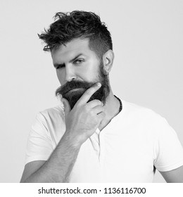Thoughtful man with long beard and mustache. Fashion model with stylish hair isolated on white. Barber fashion. Hipster in T-shirt. Brutal guy or bearded businessman. Barber fashion and beauty.