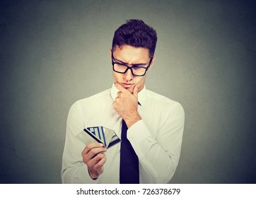 Thoughtful man with many different credit loyalty discount cards isolated on gray wall background.