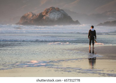 Thoughtful man on the beach looking at a lone mountain island off the coast
